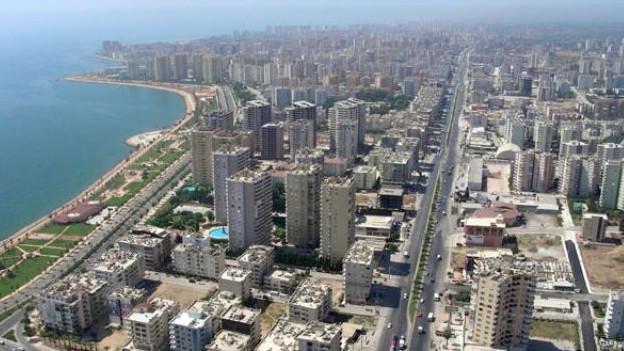 Links das Meer und eine Grünanlage am Quai, in der Mitte und rechts Hochhäuser, Wohnblocks und eine mehrspurige Strasse