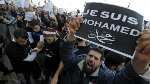 Ein Mann hält ein Schild in die Höhe auf dem steht «Je suis Mohammed».