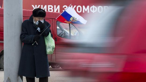 Alter Mann mit russischer Fahne auf einer Strasse, diffus im Hintergrund Fahrzeuge.