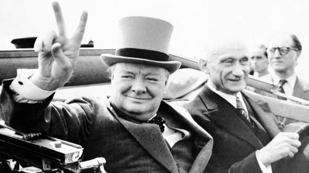 Das Bild zeigt Sir Winston Churchill in einem Auto. Er macht das Victory-Zeichen. Es ist ein altes schwarz-weiss Bild.