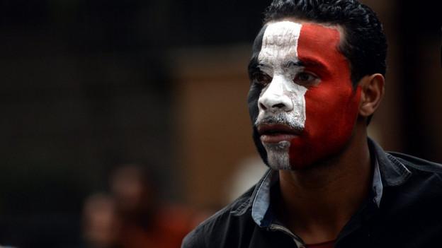 Gesicht eines Mannes, bemalt in den Farben Ägyptens: schwarz, weiss, rot.