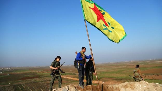 Kämpfer hissen kurdische Fahne auf einem Hügel, im Hintergund flache Landschaft.