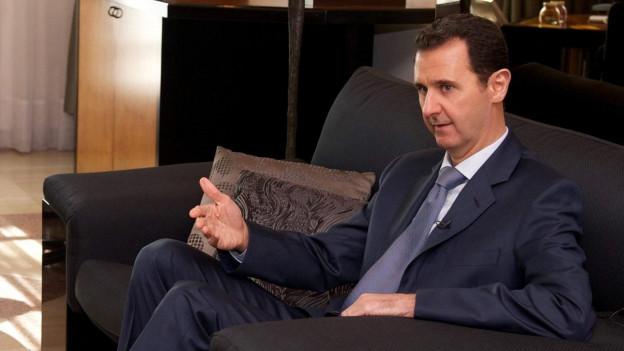 Präsident Assad im blauen Anzug sitzt in einer Polstergruppe.