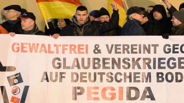 Das Bild zeigt Pegida-Demonstranten mit einem Transparent: Gewaltfrei und vereint gegen Glaubenskrieger auf deutschem Boden - Pegida.