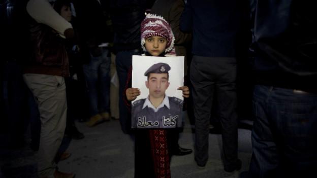 Ein Kind in Amman hält ein Foto der jordanischen Geisel in die Kamera.