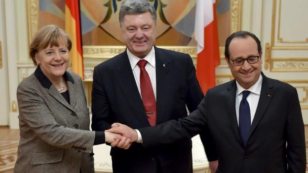Das Bild zeigt den Händedruck von Angela Merkel, François Hollande und Petro Poroschenko