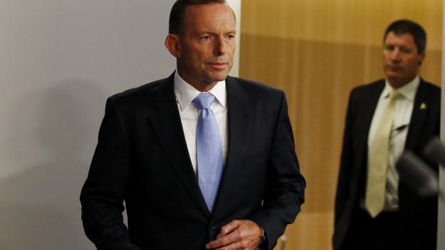 Australischer Premier Abbott mit ernstem Gesichtsausdruck (im Hintergrund verschwommen Parteikollege).