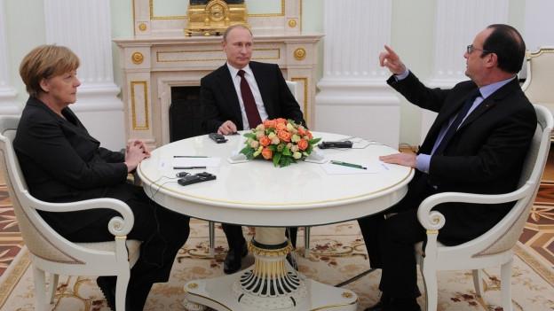 Die deutsche Bundespräsidentin Merkel, Russlands Präsident Putin und Frankreichs Präsident Hollande sitzen rund um einen Tisch.