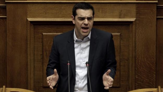 Alexis Tsipras steht an einem altehrwürdigen Renderpult aus dunklem Holz.