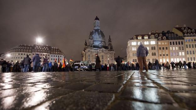 Leute auf nächlichem Platz in Dresden - im Hintergrund Frauenkirche in Desden.