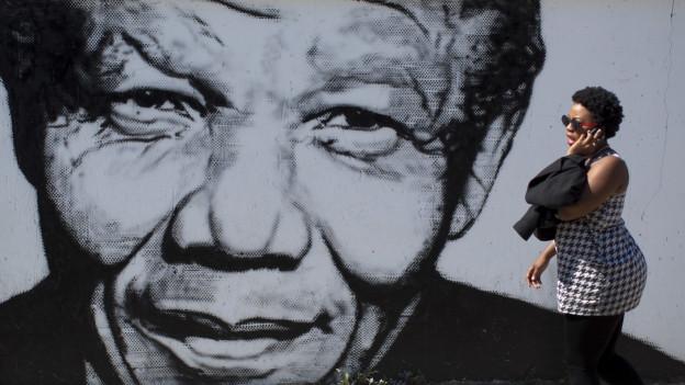 Frau mit Handy läuft vor Gross-Bild von Nelson Mandela vorbei.
