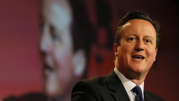Das Bild zeigt David Camerons Gesicht beim Halten einer Rede. Im Hintergrund ist sein Kopf im Grossformat an eine Wand projeziert.