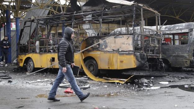 Aufnahme eines Mannes, der in Donezk vor einem zerstörten Bus vorbeiläuft.