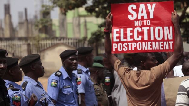 Aufnahme eines Demonstranten in Nigeria, der ein Plakat hochhält und gegen die Verschiebung der Wahlen protestiert.