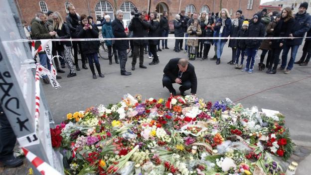 Ein grosser Haufen von Blumen am Boden, ein Mann kniet dahinter und hat den Blick zum Boden gesenkt; im Hintergrund stehen weitere Menschen hinter einem Absperrband.