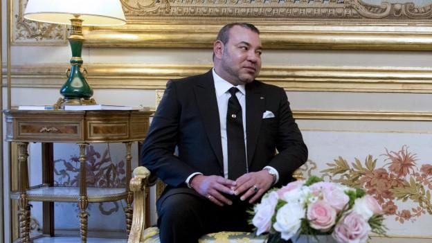 Der König von Marokko sitzt auf einem Sofa mit Blumenmuster.