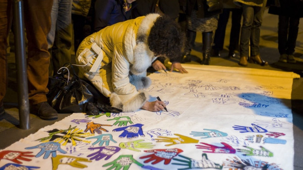 Eine Frau beugt sich über ein Tuch, auf dem viele verschieden farbige Handabdrücke aufgemalt sind.