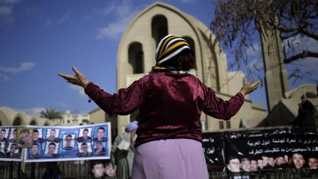Aufnahme einer Frau in Kairo, die für die 21 ägyptischen Kopten betet, welche vom IS entführt und nun ermordet wurden.