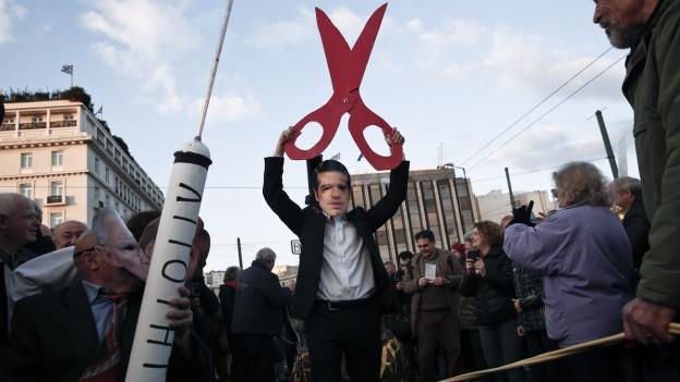 Aufnahme eines Demonstranten in Athen, der eine Maske des griechischen Premierministers Alexis Tsipras und eine grosse Schere trägt.