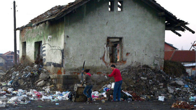 Ein Mann durchsucht Geröll und Abfall vor einem Haus.