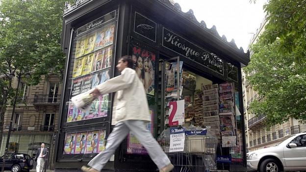 Aufnahme eines Mannes, der bei einem geöffneten Kiosk vorbeiläuft.