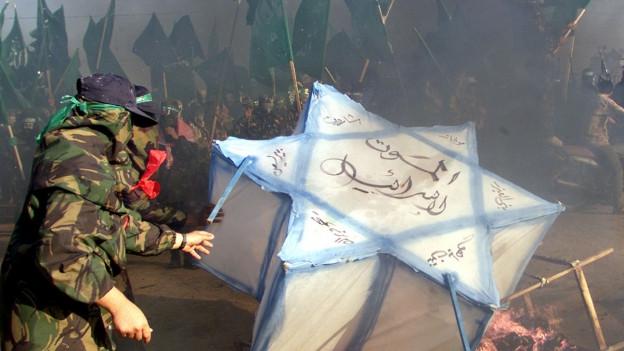 Palästineser zünden israelische Flagge an.