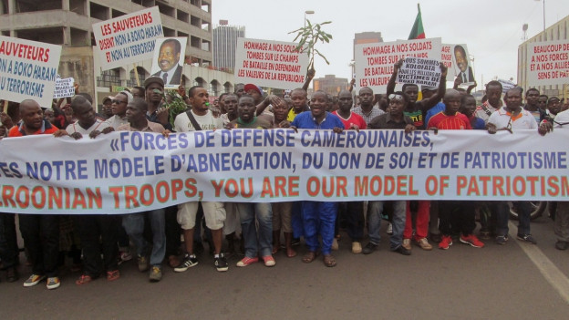 Menschenmasse in Nigeria mit Transparent demonstrieren.