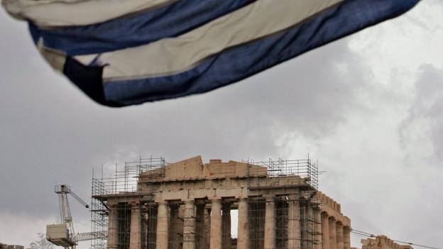 Zerschlissene griechische Fahne, im Hintergund Akropolis mit Baugerüst.