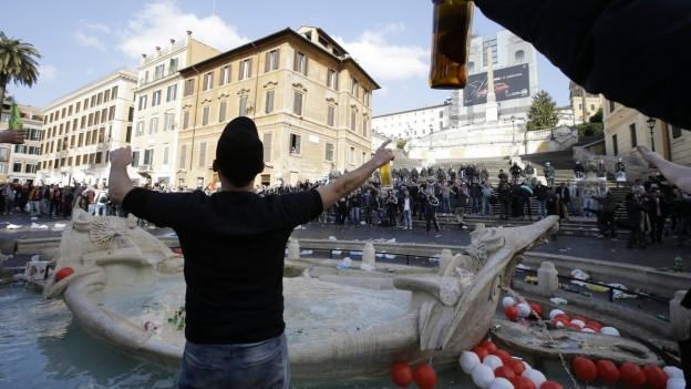 junge Männer mit Bierflschen gestukulierend vor Brunnen in Rom; im Hintergrung grölende Fans.