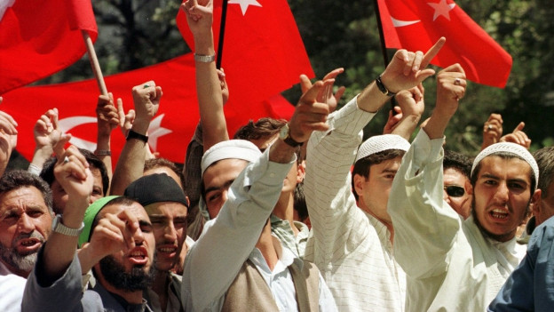 Muslime mit erhobenen Fäusten vor türkischen Flaggen.