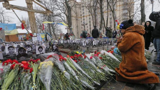 Eine Frau kniet vor Bildern von getöteten Demonstranten in Kiev