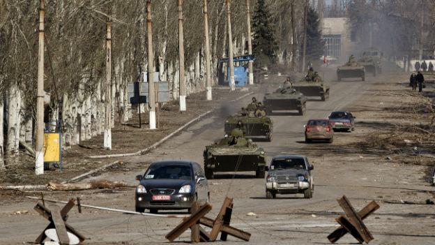 Auf einer Strasse fahren gepanzerte Fahrzeuge der Separatisten neben Autos von Zivilisten.