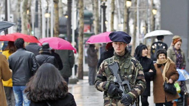 Mann im Tarnanzug und mit umgehängtem Gewehr auf dem Boulevard des Champs Elysées
