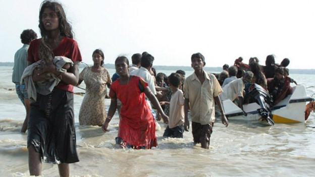 Eine Gruppe von Menschen auf der Flucht stehen knietief im Wasser am Strand im Norden von Sri Lanka.