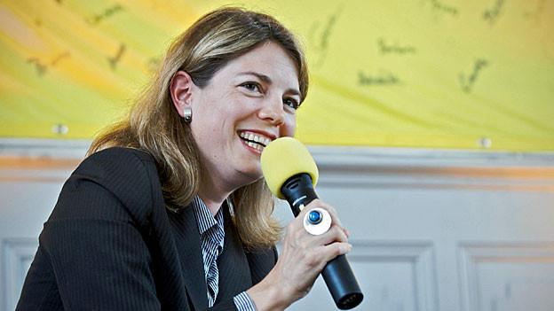 Manon Schick in dunkelblauem Blazer, mit einem gelben Mikrofon vor einer gelben-blauen Wand.