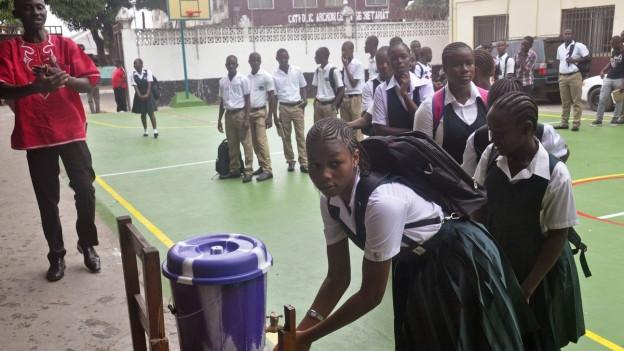 Schwarze Mädchen und Buben in Schuluniformen stehen Schlange vor einem blauen Wasserfass.