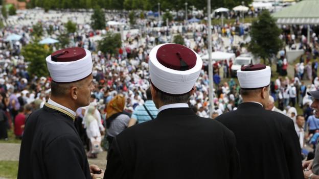 Drei muslimische Geistliche beobachten eine Beerdigungszeremonie.