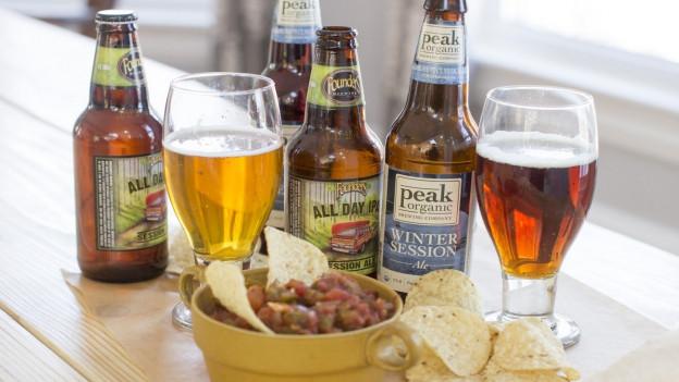 Aufnhame von verschiedenen Bierflaschen und Snacks.
