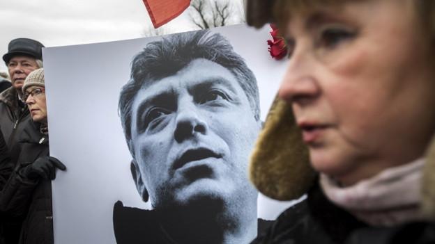 Eine Demonstrantin unscharf im Vordergrund, dahinter halten andere Menschen ein Schwarzweissbild des ermordeten Boris Nemzow.