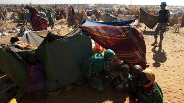 Zelte und Flüchtlinge in einem Lager in Norddarfur bewacht von einem Blauhelmsoldaten.
