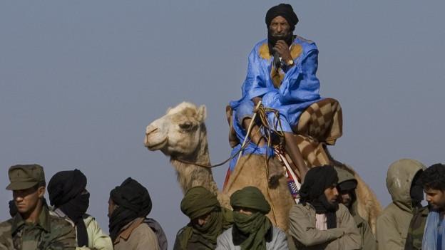Mit Kopftüchern verhüllte Männer und ein Mann in blauem Gewand auf einem Kamel.