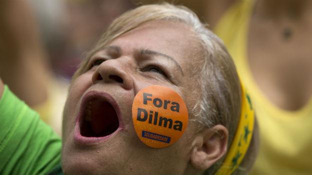 Das Bild zeigt eine Demonstrantin mit einem aufgeklebten Sticker auf dem steht: «Dilma raus».
