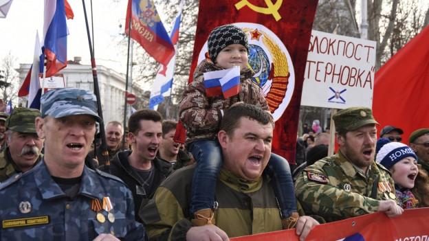Russen auf der Krim, einige in Militäruniform und mit Flaggen der Sowjetunion, nehmen an einer Kundgebung in Sewastopol auf der Krim teil, um den sogenannten Vaterlandstag zu feiern (23.2.2015).