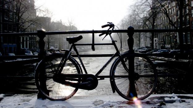Fahrrad steht auf einer Brücke in Amsterdam.