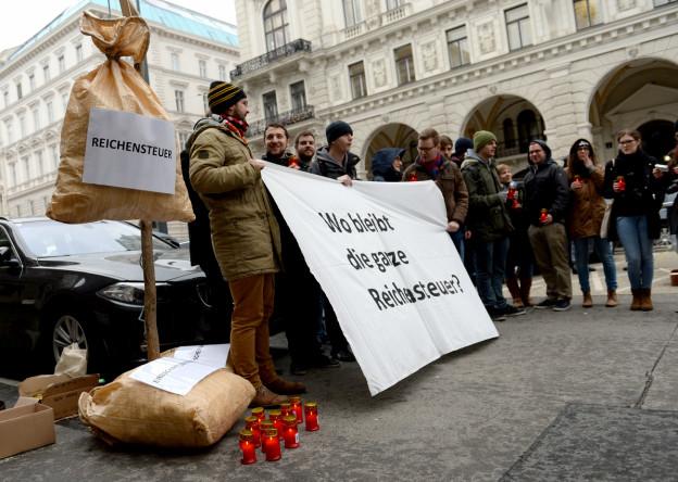 Aufnahme von Protestierenden auf der Strasse in Wien, die auf Plakaten eine Reichensteuer fordern.