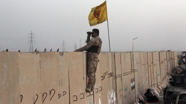 Soldat mit Fernglas schaut über eine Mauer (im Hintergrund Rauch).
