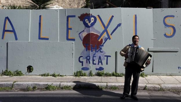 Ein Strassenmusiker spielt vor einem Graffiti in Athen, das den Support in der Bevölkerung für Regierungschef Alexis Tsipras symbolisiert. Das Bild datiert vom 21. Februar 2015.