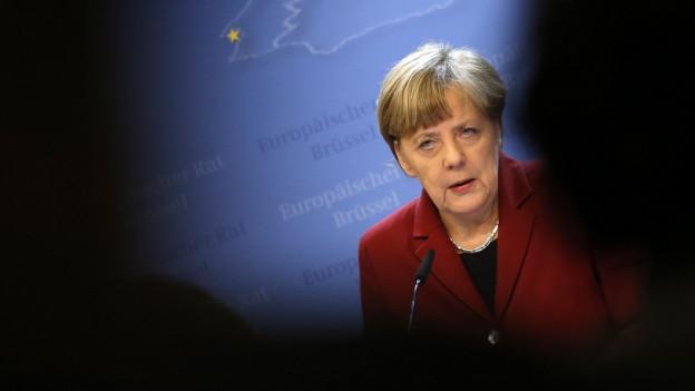 Angela Merkel vor einer blauen Wand (in einem EU-Gebäude), rund herum sind Zuhörer als schwarze Silhouetten erkennbar.