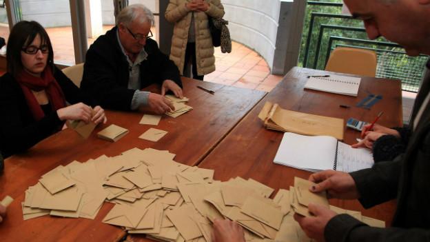 Menschen an einem Tisch zählen Stimmen aus einer Urne aus.