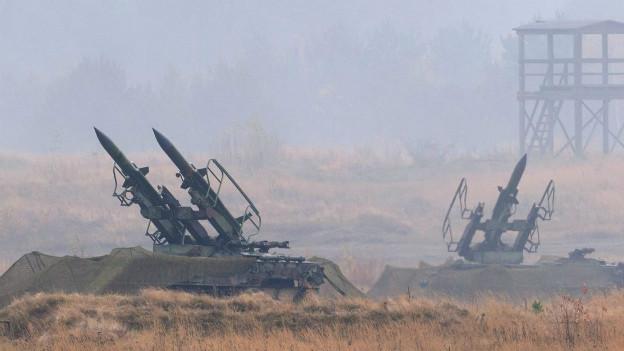 Getarnte Raketenwerfer am Boden zeigen in verschiedene Richtungen.